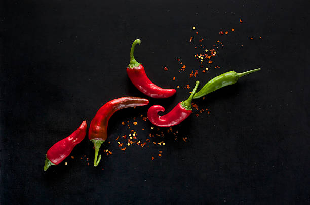 chili peppers on a black background - spaanse peper stockfoto's en -beelden