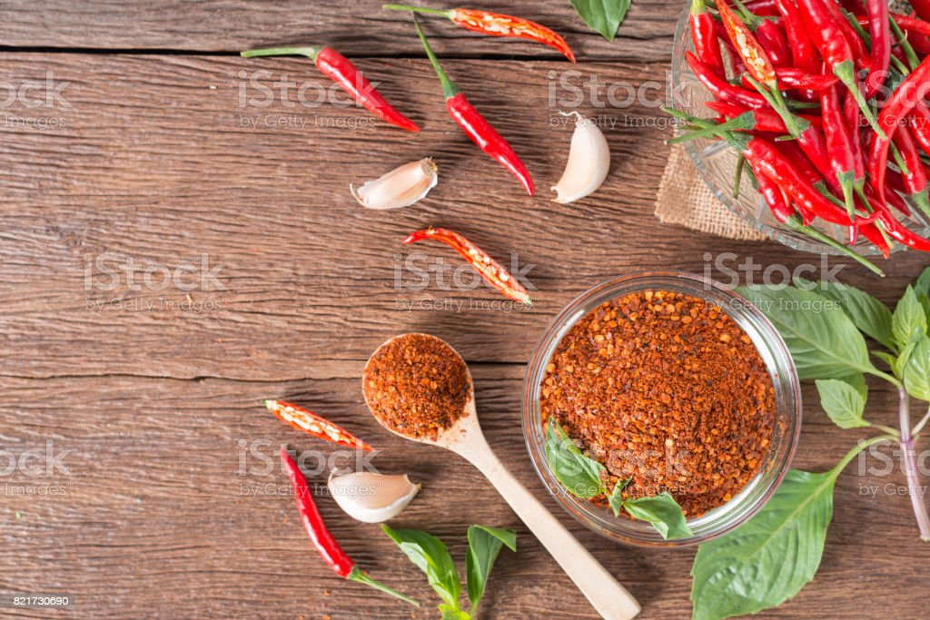 Chili powder and red chili pepper on wooden background. stock photo