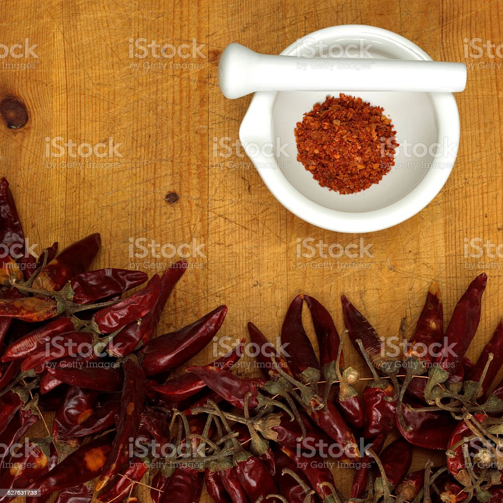 Chili powder in mortar with chillies, close-up stock photo