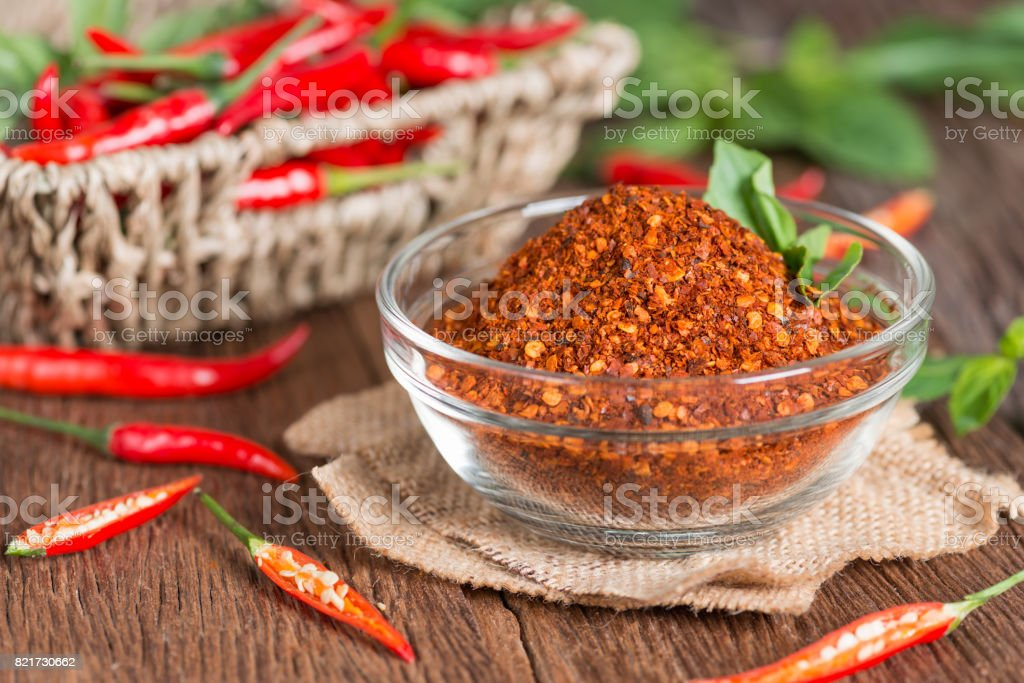 Chili powder in spoon and red chili pepper. stock photo