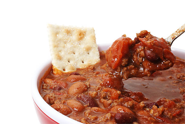 Chili with Beans and Cracker Bowl of hot chili with beans and cracker.  Isolated on white background with clipping path. chili con carne stock pictures, royalty-free photos & images