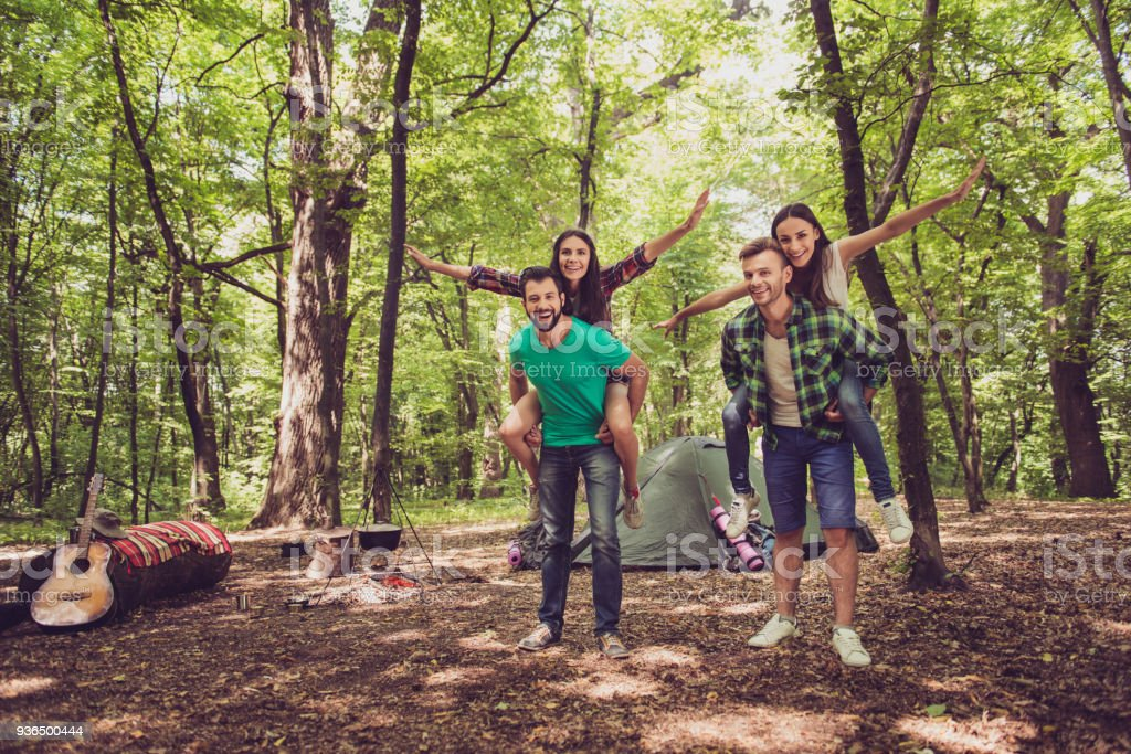 Chill Fun Joy Love And Friendship Four Friends Are Fooling Around In A Wood At A Campground Boys Piggyback Their Ladies Stock Photo Download Image Now Istock