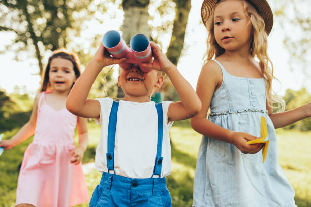 Chilldren playing with a binoculars and paper plane in summer day in park. Happy kids playing pretend safari game outdoors in the forest. Childhood concept stock photo