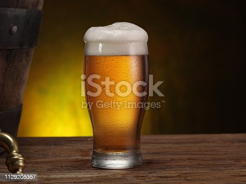 Chilled glass of beer on the wooden table. Close-up. Craft brewery.