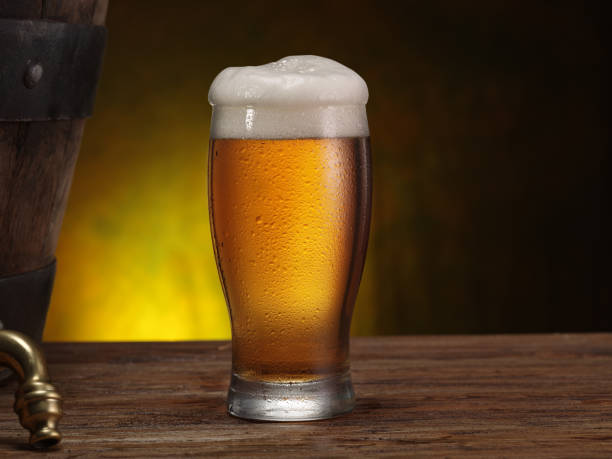 Chilled glass of beer on the wooden table. Chilled glass of beer on the wooden table. Close-up. Craft brewery. beer glass stock pictures, royalty-free photos & images