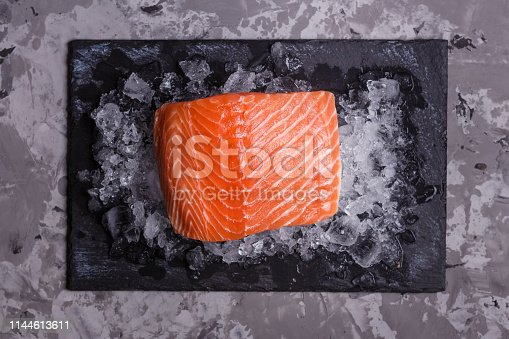 chilled salmon fillet on a gray stone background.