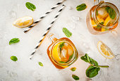 Chilled summer tea with ice, mint and lemon. Two portions in Mason Jars on a white stone table. Copy space top view