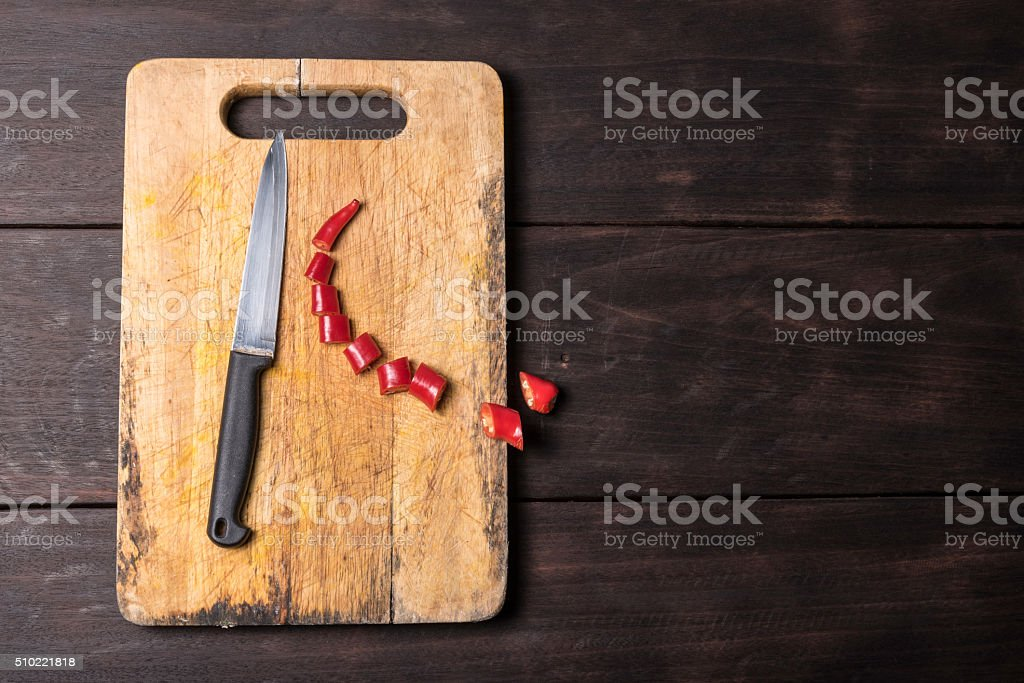 Chilli and knife with chopping block stock photo