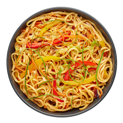 Chilli Garlic Hakka Noodles in black bowl isolated on white background. Indo-Chinese vegetarian cuisine dish. Indian veg noodles with vegetables. Classic Asian meal