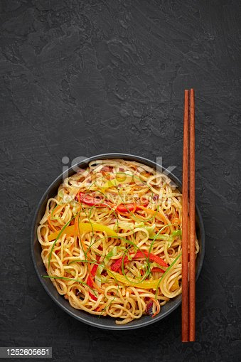 Chilli Garlic Hakka Noodles in black bowl on dark slate tabpe top. Indo-Chinese vegetarian cuisine dish. Indian veg noodles with vegetables. Classic Asian meal. Copy space. Top view