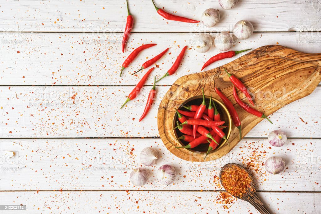Chilli Peppers And Garlic Background Red chili peppers with garlic scattered on a kitchen counter Backgrounds Stock Photo