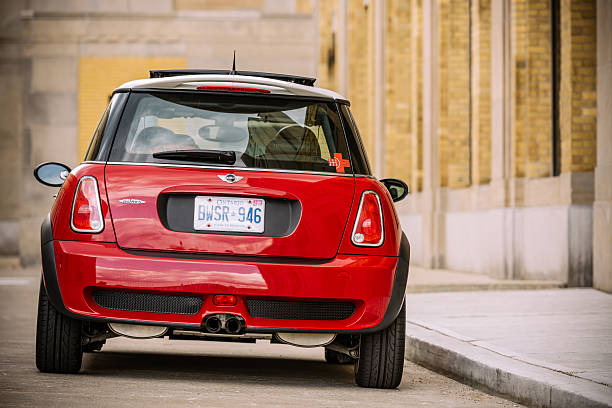 Chilli Red Mini Cooper S JCW Toronto, Ontario, Canada- July 1, 2015. 2006 Mini Cooper S JCW small vehicle parked against great architecture at The Beach area of Toronto, near Lake Ontario. This MINI Cooper S is no ordinary JCW R53 model, it is one of 64 limited edition series for Canadian market only named Competition Edition. Vehicle in the photo is #40 . Mini has been around since 1959 and has been owned and issued by various car manufacturers. It is currently distributed as a BMW brand of vehicles.  bumper stock pictures, royalty-free photos & images