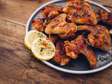 Chillie Sprinkled Spicy Chicken Wings On A Wooden Table Stock Photo - Download Image Now
