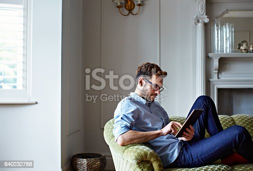 istock Chilling at home with his tablet 640232788