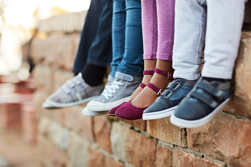 Cropped shot of unrecognizable  elementary school kids sitting on a brick wall outside