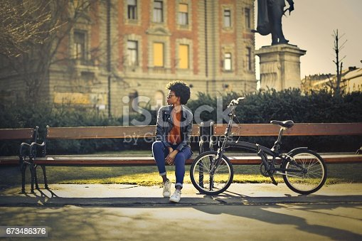 Young woman is sitting on a bench