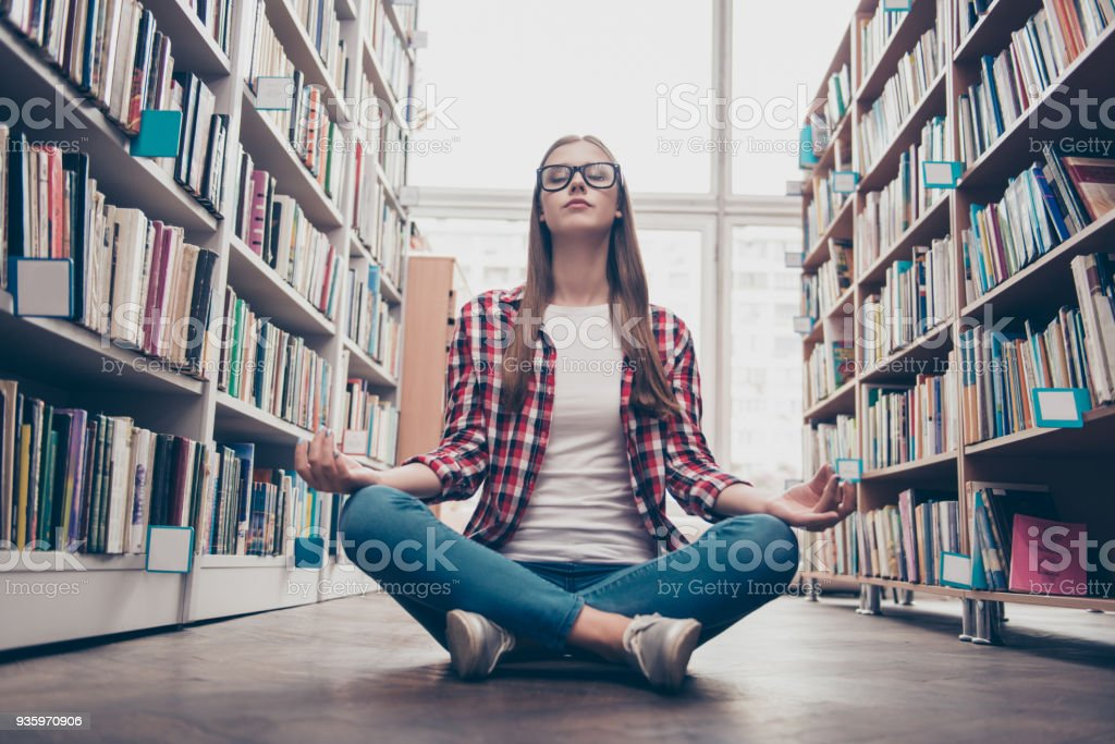 Chilling, wellbeing, vitality, peace, wisdom, education, campus lifestyle. Low angle shot of young calm nerdy girl, practicing yoga in the lotus position on floor in archive room of library stock photo