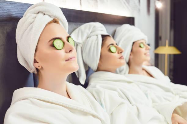 chilling women in bathrobes with cucumber slices on face - viziarsi foto e immagini stock