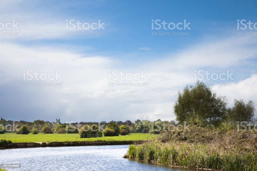 chilly springtime sun on famous beauty spot of River Stour with Dedham church in distance in Essex England royalty-free stock photo