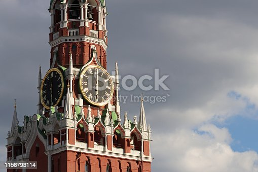 Moscow Kremlin tower clock against dramatic sky with clouds, time concept