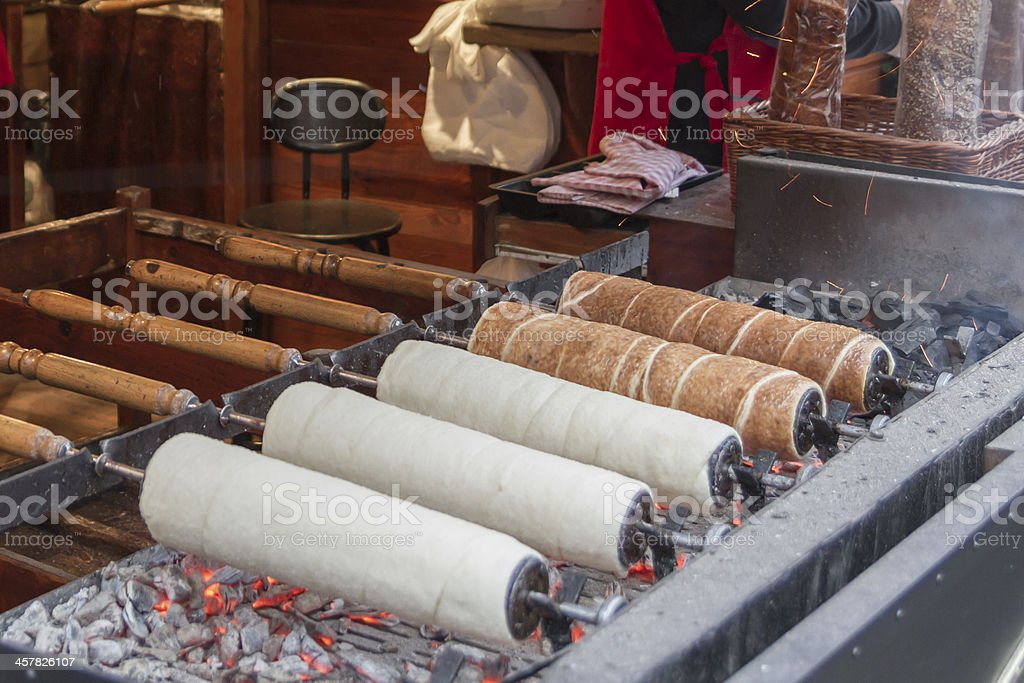 Chimney cake baking on a spit over charcoal fire stock photo