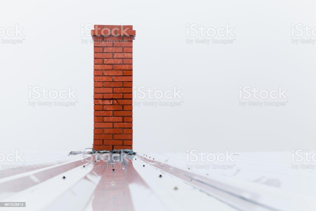 Chimney made of red bricks over white sky stock photo