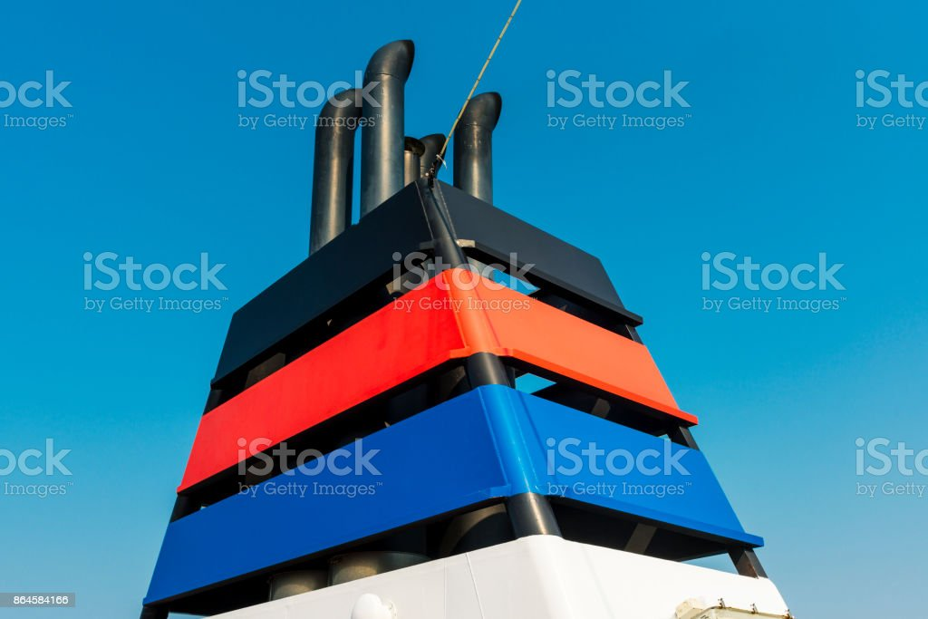 chimney of a ship in front of a blue sky stock photo