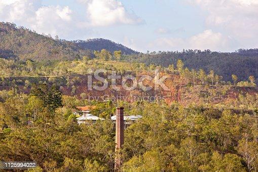 Tall brick chimney stack at the abandoned Mt Morgan gold mine, falling into disrepair