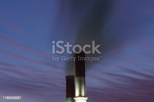 Heat station pipes. Smoking pipes on blue sky background in winter. Factory chimneys, concept of industry and ecology, heating season, modern global warming, air pollution.