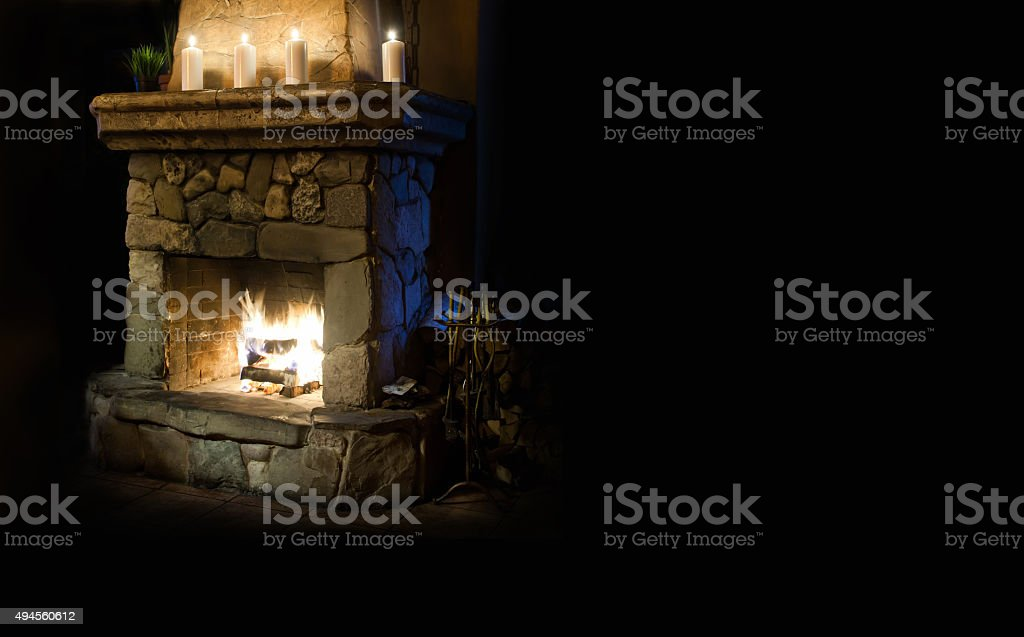 Chimney place with candles  and flame. Copy space, black background stock photo