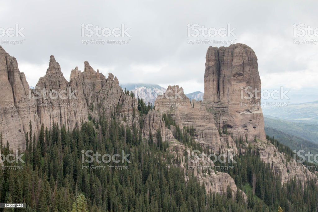 Chimney rock with jagged mountain range in the Uncompahgre National Forest stock photo