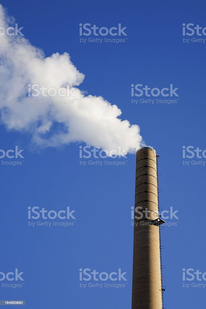 Chimney stack in front of deep blue sky royalty-free stock photo