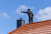 FISCHBACH, GERMANY - March 21 2018: Chimney sweep cleaning a chimney standing on the house roof, lowering equipment down the flue