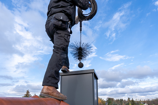 Chimney sweep cleaning a chimney standing on the house roof, lowering equipment down the flue