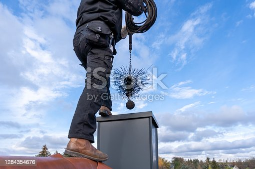istock chimney sweep with stovepipe hat upon the roof 1284354676