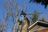 Man working, cleaning out chimney at top of house.