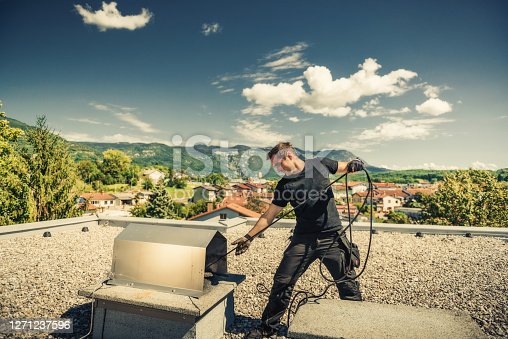 Chimney sweeper cleaning a chimney on top of the roof