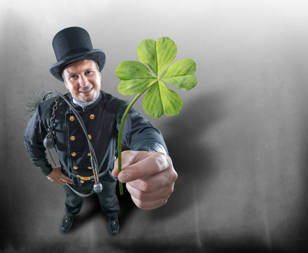 Chimney sweeper offering four leaf clover for New Year celebration stock photo