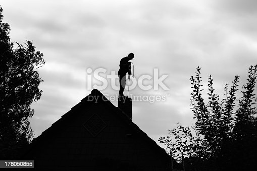 istock Chimney sweeper working on the roof 178050855