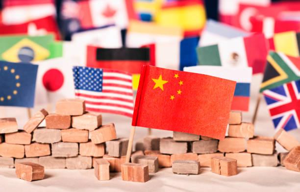 China als wirtschaftliche und politische Macht Flagge Chinas vor Flaggen vieler anderer Länder als Symbol für seine wirtschaftliche und politische Macht foreign affairs stock pictures, royalty-free photos & images