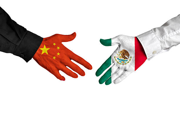 China and Mexico leaders shaking hands on a deal agreement stock photo