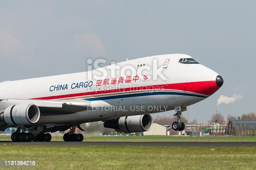 A Boeing 747 from China Cargo touches down on runway 18R at Amsterdam Schiphol Airport.  The airport code for Schiphol is AMS.