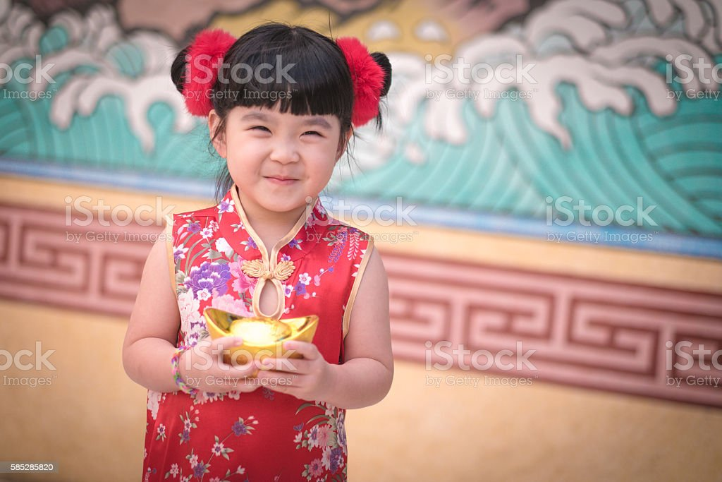China girl in traditional chinese dress greeting holding a gold china girl in traditional chinese dress greeting holding a gold royalty free stock photo m4hsunfo