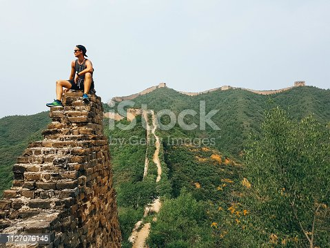 A man sitting on the Great Wall in China. There are still hidden gems at this so popular travel destination.