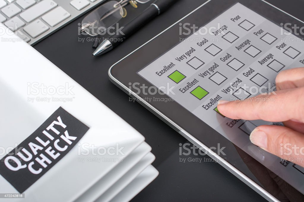 Quality check on a digital tablet finger tabs on Excellent next to a...