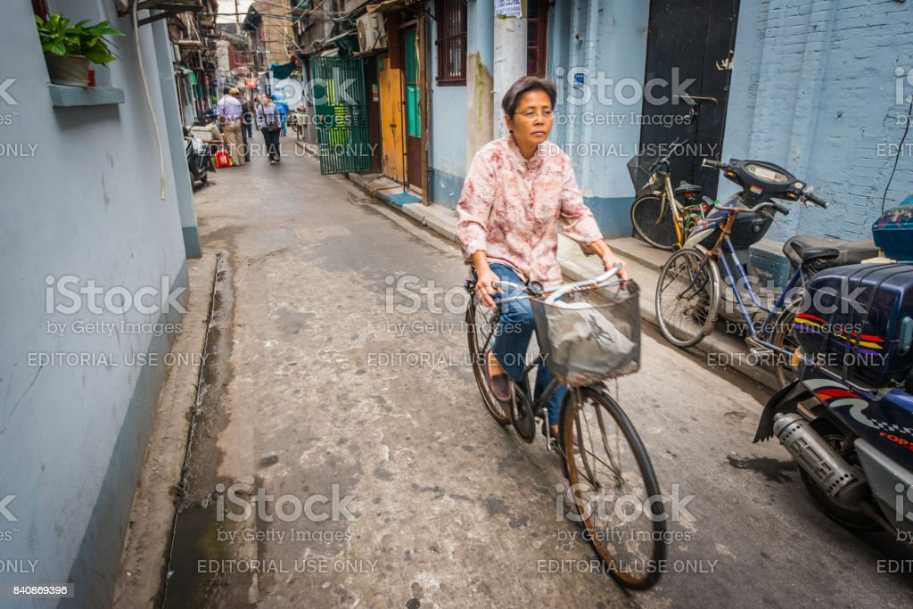 Woman cycling through the busy narrow alleyways of Shanghai\'s Old...
