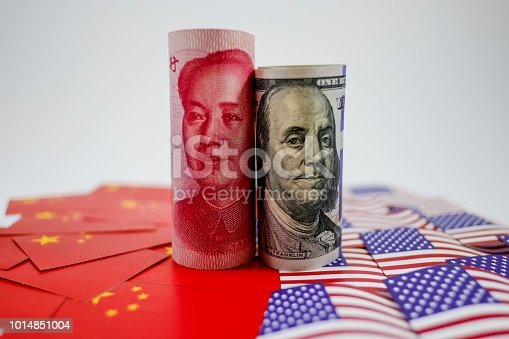 istock China yuan banknote on China flags and US dollar banknote on united states flags for trade war 1014851004