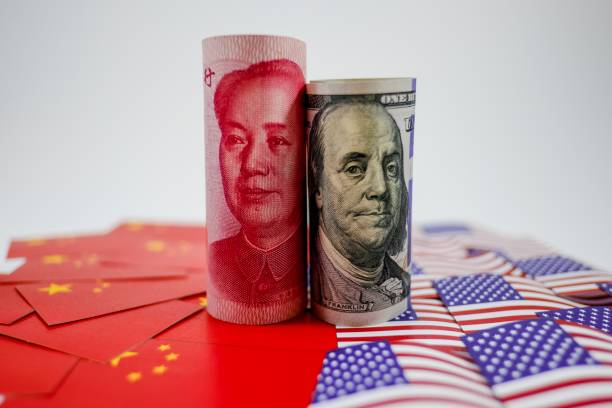 China yuan banknote on China flags and US dollar banknote on united states flags for trade war stock photo