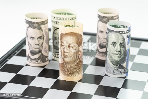 928696036 istock photo China Yuan banknote roll at front surrund with US Dollar banknote roll on chessboard, United States and China tarrif trade war, global financial economy money game concept 1027441788