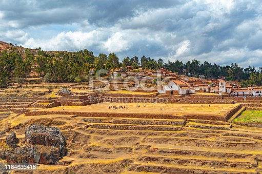 The inca agriculture terraces and inca ruin of Chinchero, incidental tourists walking and its spanish colonial style architecture with town square and church, Sacred Valley, Cusco Region, Peru.